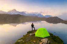 Rear View Of Man With Hat Standing Outside Tent At Obere Schwarziseeli Lake At Dawn, Furka Pass, Canton Uri, Switzerland