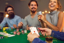 Mans Hands Holding Playing Cards, Poker Chips And Drink In Glass During Poker Gambling
