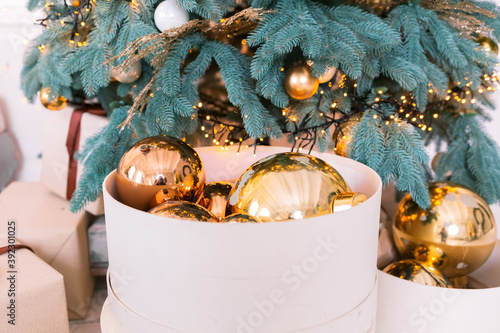 Tela Golden Christmas balls in a round gift box under the Christmas tree