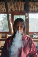 Woman Exhaling Smoke Through N...