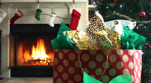 Christmas Decorations Home Living Room With Wrapped Present Gift Bag Package Filled With Tissue Paper Sitting Below Christmas Tree With Holiday Season Stockings Hanging Above Fireplace In Background