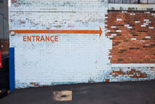 Entrance Sign On A Brick Wall
