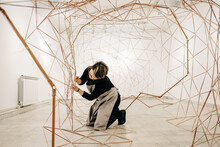 Female Artist Working On A Large Metal Sculpture In The Empty Art Gallery