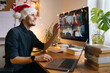 Young man having Zoom video call via a computer in the home office. Christmas Day party. Virtual happy hour wine Stay at home and work from home concept during Coronavirus pandemic. Man in santa hat