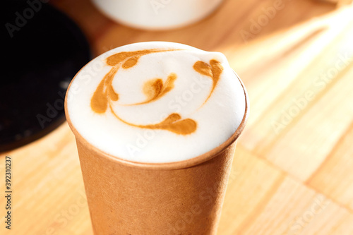 Fotografia Cup of coffee to go on the wooden table with latte art