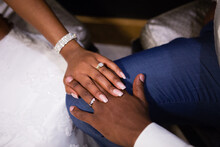 Just Married Young African Couple's Hands, Holding Together, New Golden Rings With Diamonds, Long Fingers, Wedding Manicure, Shiny Wedding Bracelet, White Dress, Blue Groom's Suit, White Shirt
