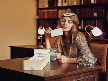 Young Beautiful Fashionable Model Sits In A Library And Plays Cards