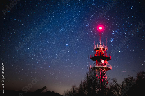 Valokuva Big red antenna tower lit by red light under a beautiful starry night