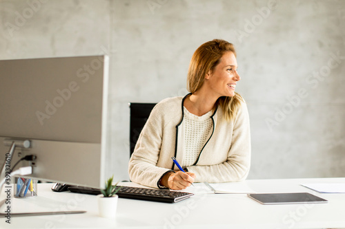Bbeautiful businesswoman working on laptop in bright modern office
