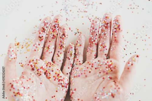 Colorful glitters on female's hands, close up, top view Fototapet