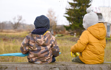 Small Children Sit On A Makeshift Bench With Their Backs To It. Sister And Brother Walking On An Autumn Day