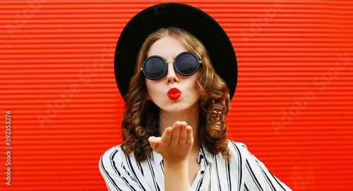 Portrait of beautiful young woman blowing red lips sending sweet air kiss wearin Wallpaper Mural