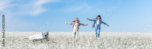 Photo Young aviators with an airplane in the field