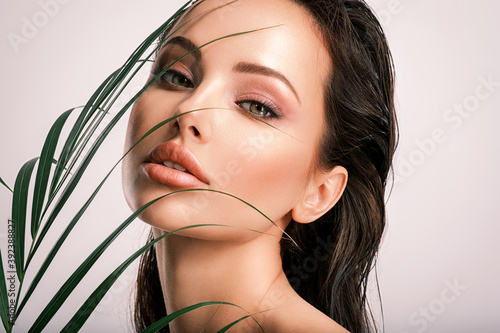 Young beautiful woman with green leaves near face and body. Skin care beauty treatments concept.  Closeup girl's face with green leave. White model with clean, health skin of face - posing at studio - fototapety na wymiar