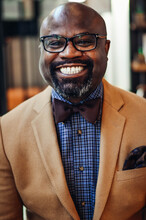 Portrait Of Confident African American Businessman In Glasses And Tan Blazer.