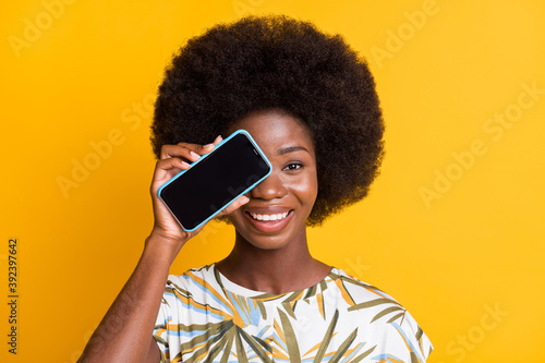 Portrait of nice cool curly hair lady showing telephone cover eye wear print t-shirt isolated over yellow color background