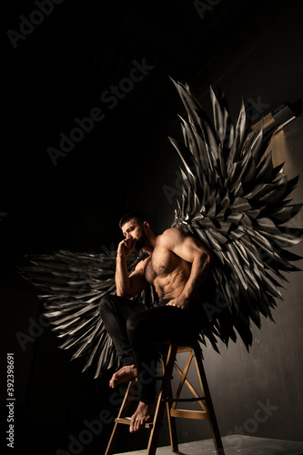 Fotografering handsome athletic man in black angel costume on black background