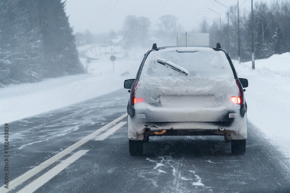 Fototapeta Car is driving on a winter road in a blizzard