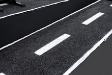 Black Asphalt Road With White Dividing Lines.Traffic Lines On The Street.
