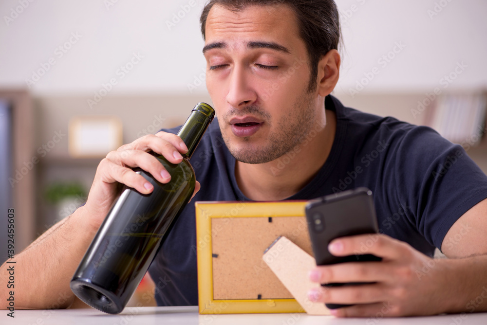 Fototapeta Young male alcoholic suffering from unhappy love at home