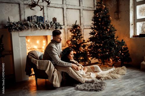 Foto Beautiful couple sit near fireplace and Christmas tree, charming husband hugging