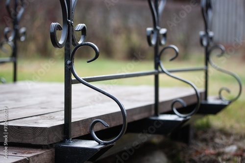 Fotografía Garden bridge with black wrought iron balusters against the background of a gree