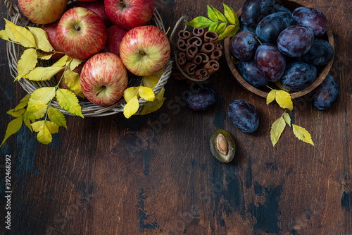 Fotografija Fresh, ripe apples and plums with cinnamon sticks on a wooden table