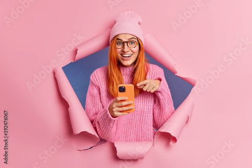 Foto Positive redhead woman points at display of modern smartphone gets useful information from intenet surfs in social networks giggles positively uses mobile app or new technology