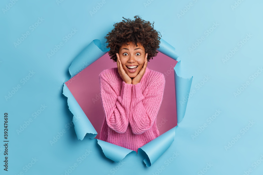 Fototapeta Positive dark skinned ethnic woman feels excited and glad keeps hands on cheeks hears excellent news impressed to hear something awesome stands through paper background. Human emotions concept