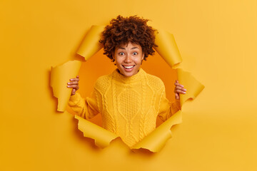 Panel Szklany Boks Cheerful smiling young dark skinned Afro American woman poses in torn paper studio wall looks happily at camera feels delighted has good mood wears yellow jumper. Human positive emotions concept