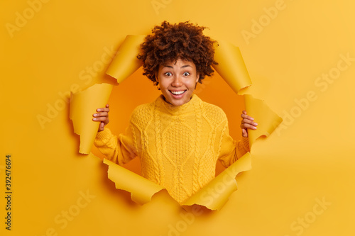 Foto Cheerful smiling young dark skinned Afro American woman poses in torn paper studio wall looks happily at camera feels delighted has good mood wears yellow jumper