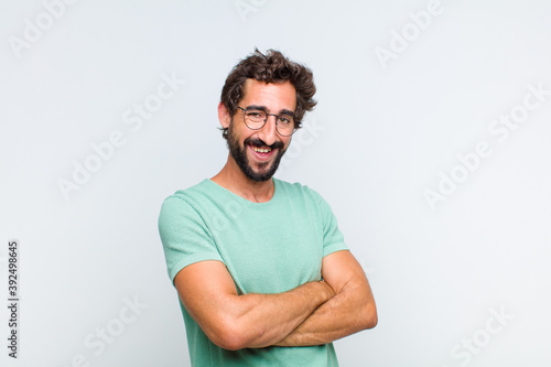 young bearded man looking like a happy, proud and satisfied achiever smiling wit Canvas Print