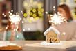 Leinwandbild Motiv Tasty gingerbread house standing on table against sparkling bengal lights