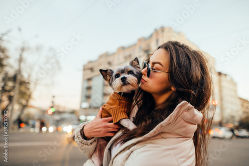 Obraz na plátně Portrait of a stylish woman standing with a dog in her arms on a background of cityscape, looking to the side