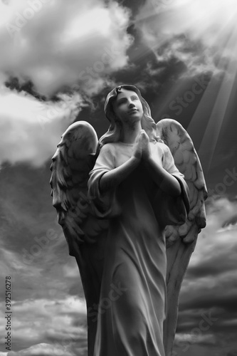 Human soul as angel with wings looking up at the sky in rays of light Fotobehang