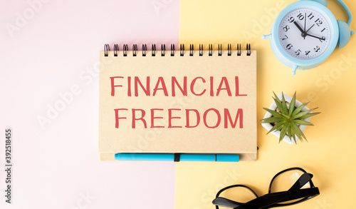 Fototapeta Financial freedom. Text financial freedom written in notepad. Pensil, calculator and magnifier on a wooden background. business concept. Business and Finance. obraz