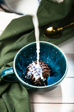 Cocoa Bomb That Melts With Hot Milk.  Cup Of Dark Hot Chocolate. Milk Splash. Comfort Food. White Wood Table With Green Cloth And Golden Spoon.