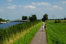 Kinderdijk, The Netherlands, August 2019. A Small Road Winds Through The Dutch Countryside, Lined With Green Grass And A Canal, Some Boys Are Walking Along It. On The Left A White Bridge.
