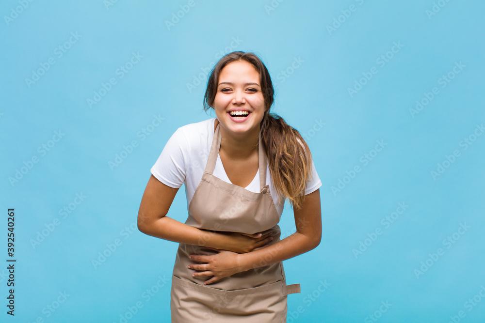 Fototapeta young hispanic woman laughing out loud at some hilarious joke, feeling happy and cheerful, having fun