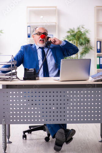 Old businessman clown working in the office Fototapeta