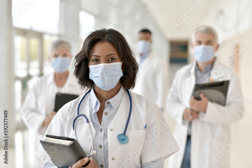 Photo Group of doctors standing in hospital corridor with face mask
