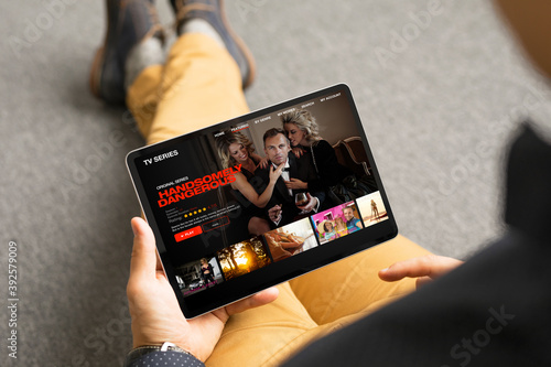 Obraz Man looking TV series and movies via streaming service on his digital tablet - fototapety do salonu