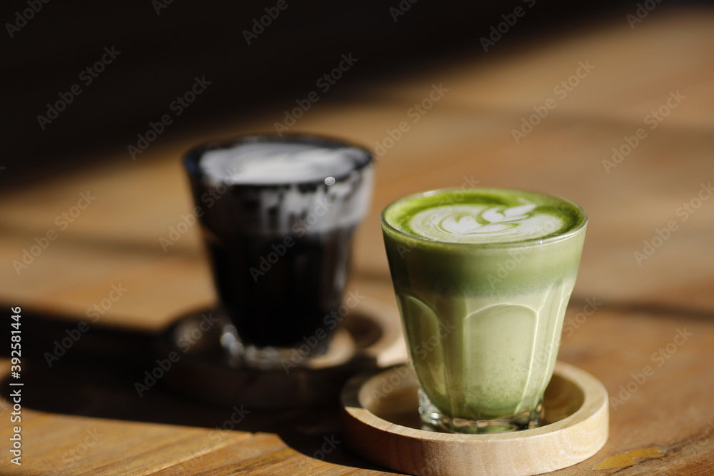 Fototapeta Cup of hot Japanese matcha green tea latte with tulip pattern on rustic dark wooden table with copy space
