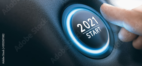 Obraz Start-stop engine button with a sign 2021 and a finger near it. New Year. - fototapety do salonu