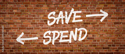 Save or Spend written on a brick wall