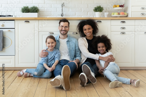 Obraz Portrait happy multiracial family sitting on warm wooden floor in modern kitchen at home, smiling Caucasian father and African American mother hugging two little daughters, posing for photo together - fototapety do salonu