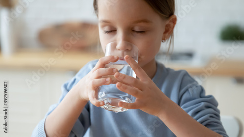 Fototapeta Close up dehydrated thirsty pretty little girl enjoying pure mineral water, hold