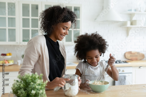 Smiling African American mother with little daughter cooking pancakes, standing Fototapeta