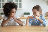 Cute smiling diverse little girls drinking fresh water, sitting at wooden table in kitchen, looking at each other, multiracial sisters adorable kids enjoying aqua, refreshment concept