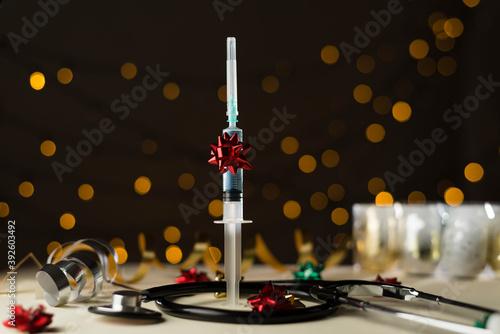 Foto Jeringuilla vacuna covid-19 y estetoscopio sobre mesa de color cálido, coronavir
